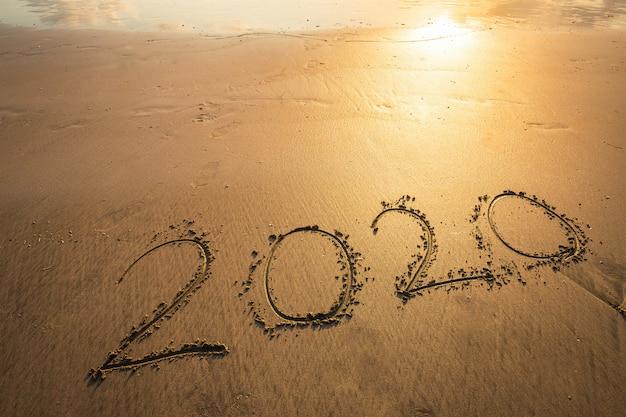 Feliz año nuevo 2020 texto en la hermosa playa del mar con ola amanecer temprano en la mañana sobre el horizonte