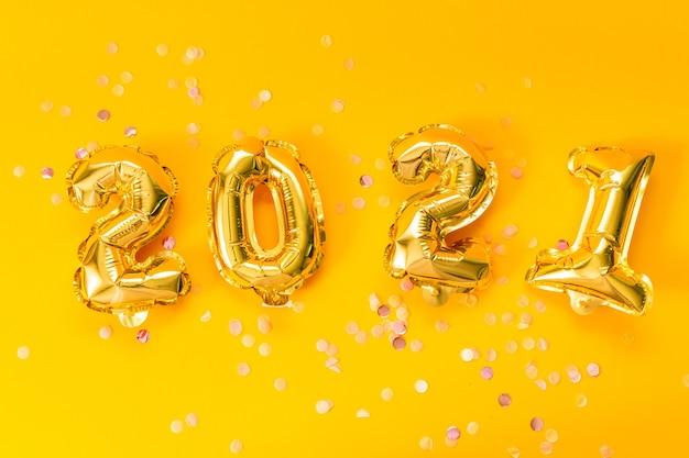 Feliz año nuevo 2021 celebración. globos dorados brillantes con estrellas brillantes sobre un fondo amarillo.