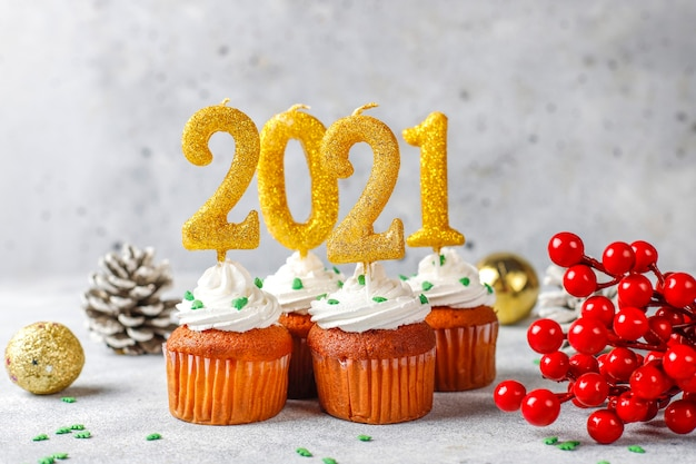 Feliz año nuevo 2021, cupcakes con velas doradas.