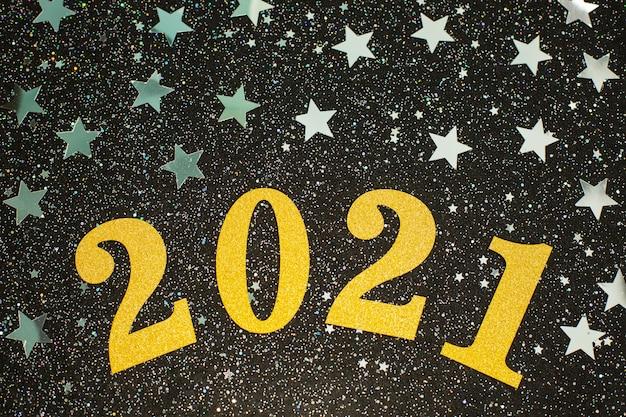 Feliz año nuevo 2021 con estrellas de brillo plateado sobre fondo negro.