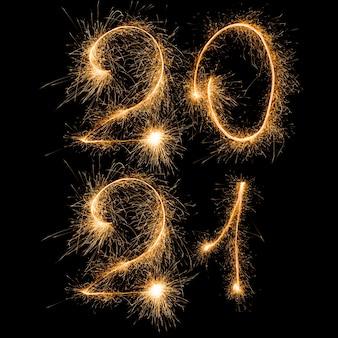 Feliz año nuevo 2021. número 2021 escrito brillantes bengalas en dos líneas aisladas sobre fondo negro con espacio de copia para texto.