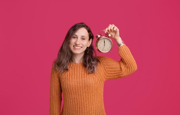 Feliz año nuevo, alegre joven sosteniendo despertador sobre espacio rosa