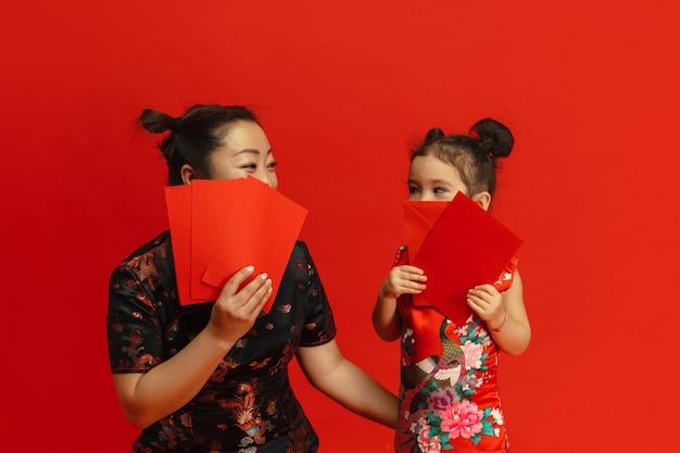 Feliz año nuevo chino. retrato de madre e hija asiática aislado sobre fondo rojo.