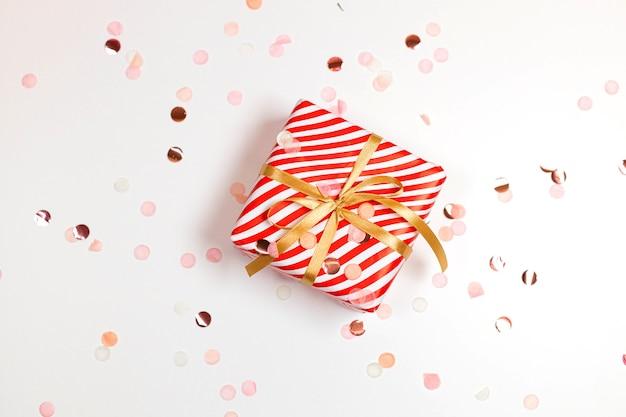 Feliz año nuevo composición horizontal. caja de regalos de diseño de rayas de navidad, lazo dorado, luz brillante sobre fondo blanco con espacio de copia. endecha plana, vista superior