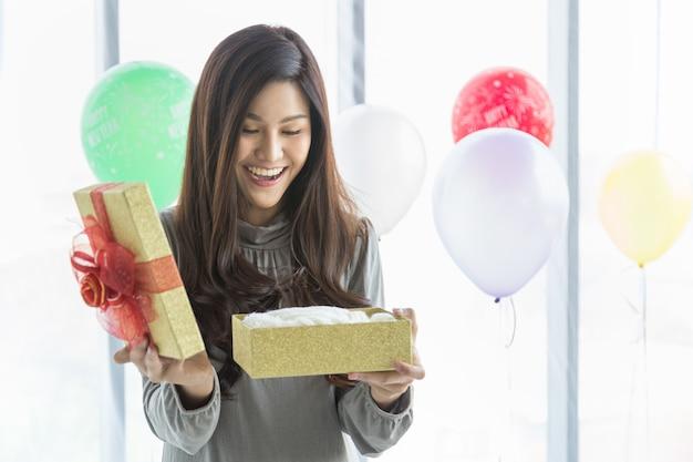 Feliz año nuevo y concepto estacional de vacaciones. retrato de la mujer joven asiática hermosa que sonríe y sorprendida con la caja de regalo con el globo colorido como fondo.
