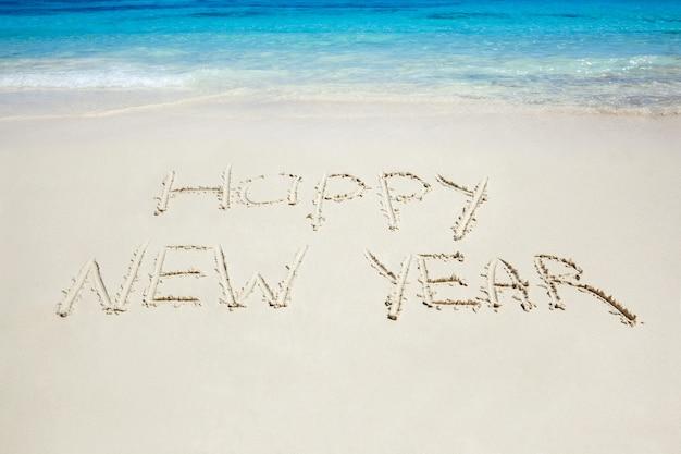 Feliz año nuevo escrito en la playa de arena. celebración tropical gira de año nuevo