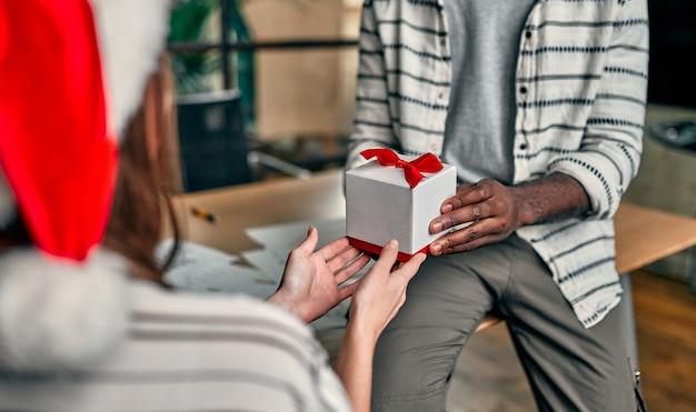¡feliz año nuevo y feliz navidad! jóvenes creativos multirraciales que llevan gorros de papá noel intercambian regalos con sus colegas el último día laborable.