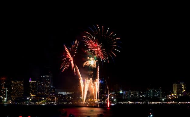 Feliz año nuevo fuegos artificiales sobre el paisaje urbano en la noche. festival de celebración de vacaciones