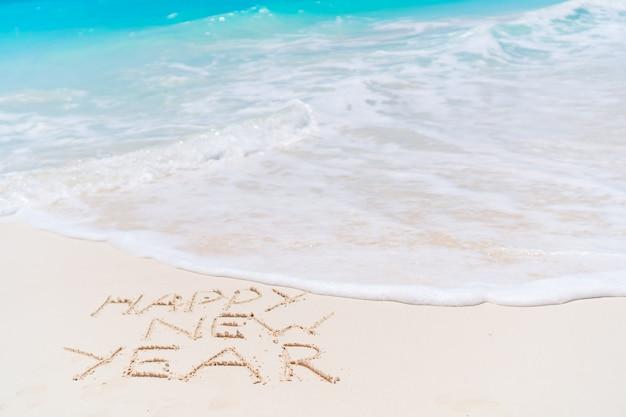 Feliz año nuevo inscripción escrita en playa de arena