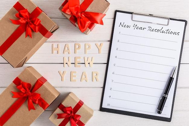 Feliz año nuevo lista de resoluciones de madera y año nuevo escrita en el portapapeles con caja de regalo