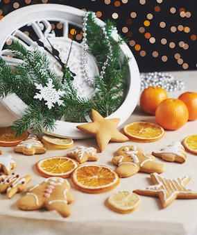 Feliz año nuevo a la medianoche, antiguo reloj de madera con luces navideñas y ramas de abeto. cocinar y decorar galletas de jengibre navideñas y rodajas de naranja fritas