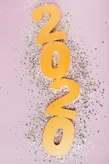 Feliz año nuevo con números dorados 2020 y brillo plateado