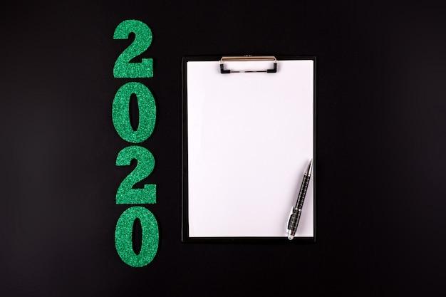 Feliz año nuevo. números verdes sobre fondo negro y tarjeta de felicitación en blanco