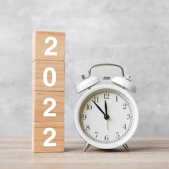 Feliz año nuevo con reloj despertador vintage y bloque 2022. navidad, nuevo comienzo, resolución, cuenta atrás, metas, plan, acción y concepto de motivación