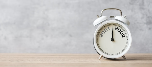 Feliz año nuevo con reloj despertador vintage y cambio 2021 al número 2022. feliz navidad, nuevo comienzo, resolución, cuenta atrás, metas, plan, acción y concepto de misión