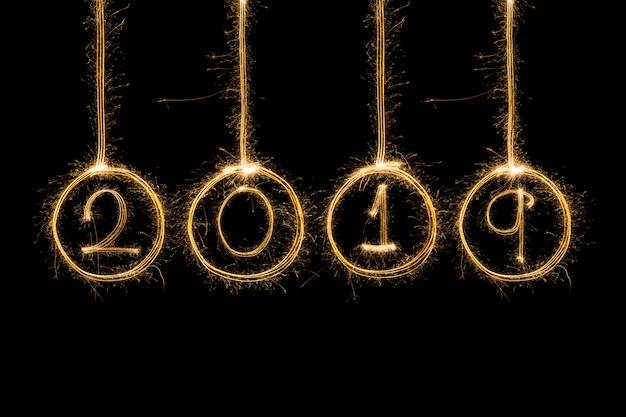 Feliz año nuevo texto escrito con fuegos artificiales sparkle aislados sobre fondo negro