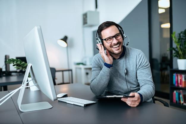 Feliz apuesto agente de soporte técnico hablando con un cliente.