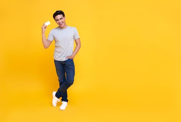 Feliz apuesto hombre asiático adicto a las compras que muestra la tarjeta de crédito en la mano en amarillo.