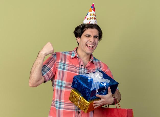 Feliz apuesto hombre caucásico con gorro de cumpleaños mantiene el puño sostiene cajas de regalo y bolsa de papel