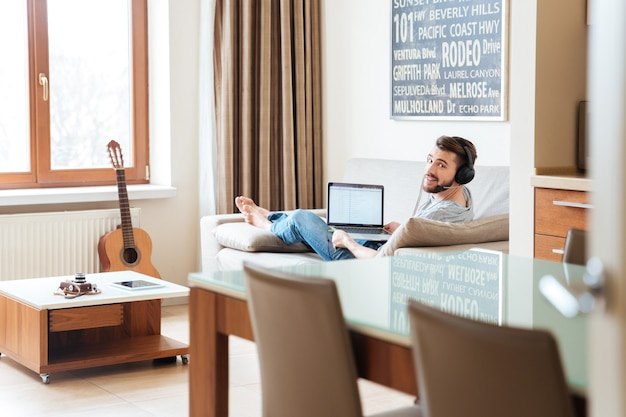 Feliz apuesto joven en auriculares acostado en el sofá y escuchando música desde la computadora portátil en casa