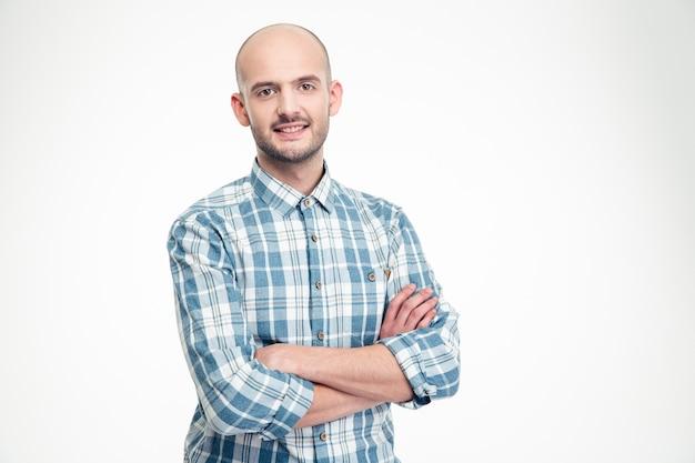 Feliz apuesto joven en camisa a cuadros de pie con los brazos cruzados sobre la pared blanca