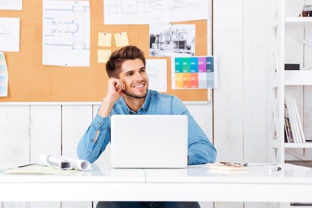 Feliz apuesto joven empresario sentado en su lugar de trabajo en la oficina y hablando por teléfono móvil