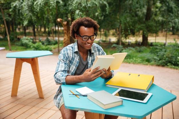 Feliz apuesto joven con gafas leyendo y leyendo en la cafetería al aire libre