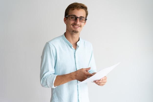 Feliz apuesto joven en gafas trabajando con papel y mirando a cámara.