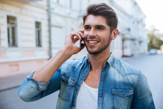 Feliz apuesto joven hablando por teléfono celular al aire libre