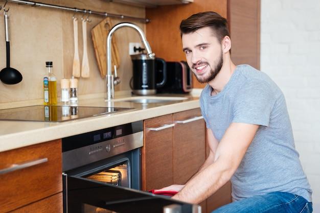 Feliz apuesto joven horneando galletas en la cocina de casa