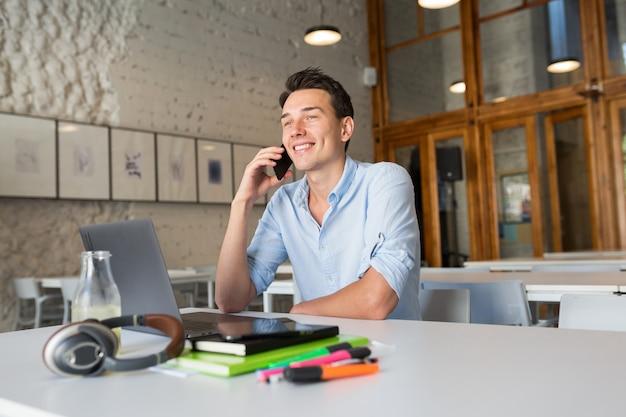 Feliz apuesto joven sentado en la oficina de trabajo conjunto
