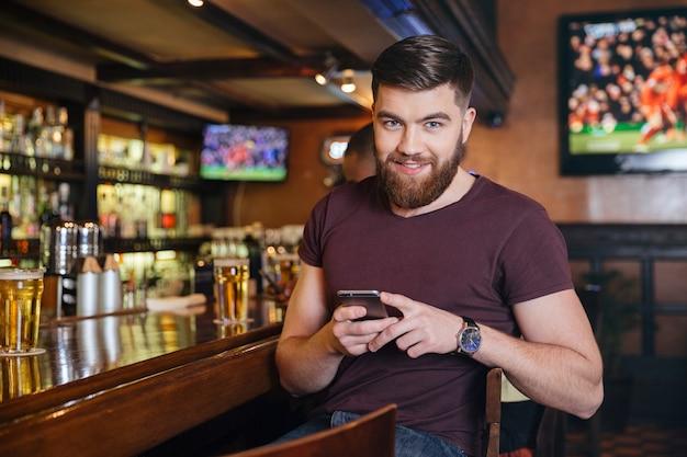 Feliz apuesto joven sentado y mediante teléfono móvil en el pub