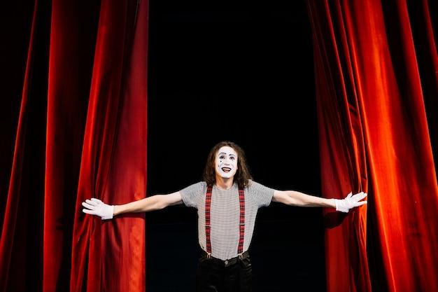 Feliz artista mimo masculino cerca de la cortina roja