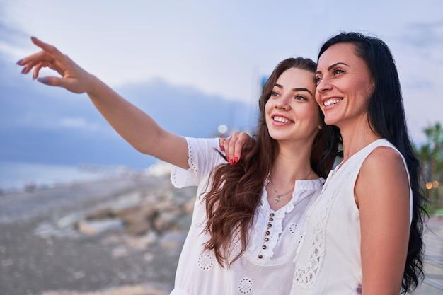 Feliz atractiva hija abrazando sonriente con madre riendo y mirando juntos en la distancia en verano