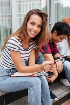 Feliz atractiva joven sentada y usando teléfono celular al aire libre