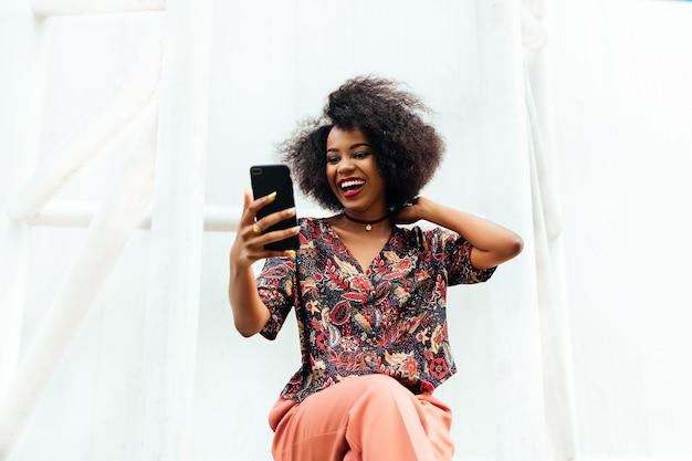 Feliz atractiva mujer africana, sonriendo alegremente mientras mira la pantalla del teléfono móvil.