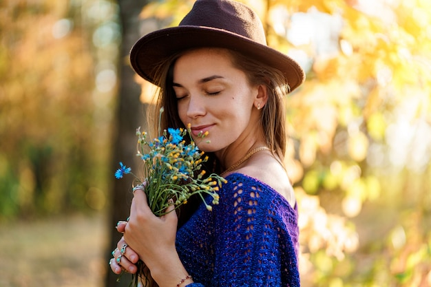 Feliz atractiva mujer morena de otoño con cabello largo en un sombrero marrón y un suéter azul de punto disfruta del aroma de las flores silvestres en el bosque de otoño al aire libre en otoño