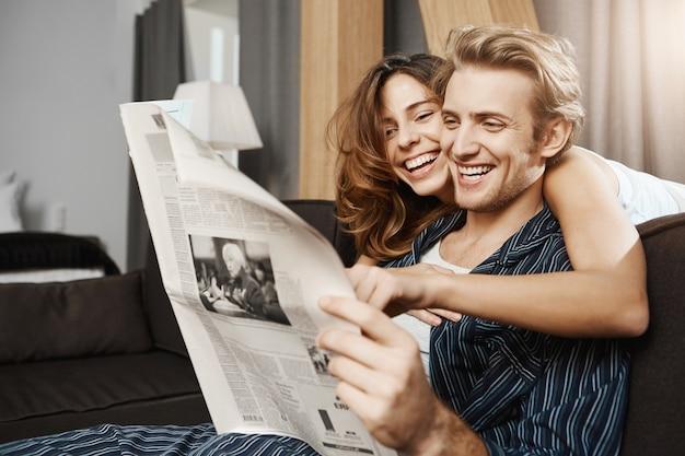 Feliz y atractiva pareja de enamorados leyendo el periódico en casa