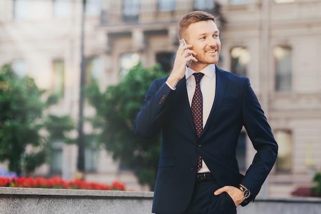 Feliz atractivo financiero masculino en ropa elegante, utilizando teléfonos inteligentes modernos