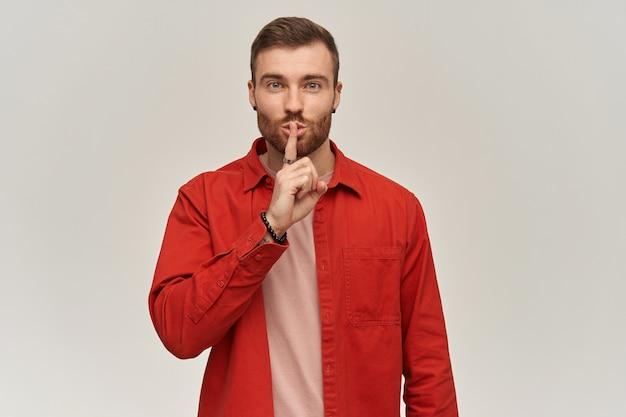 Feliz atractivo joven barbudo en camisa roja mostrando gesto de silencio y mirando al frente sobre la pared blanca