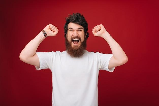 Feliz barbudo gestos masculinos activamente, expresa emociones positivas. concepto de felicidad y lenguaje corporal