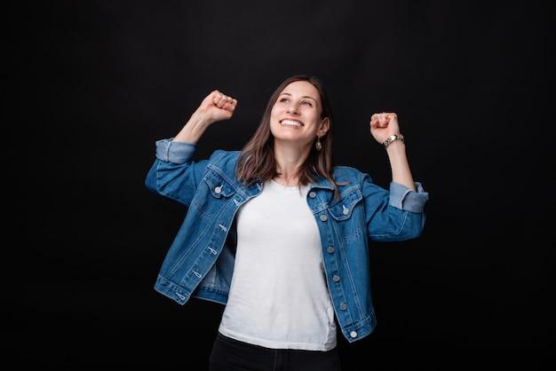 Feliz bastante joven celebrando el éxito con las manos en alto y sonriendo
