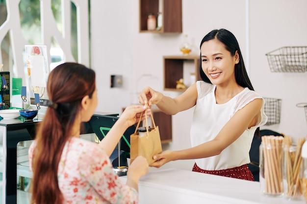 Feliz bastante joven dependienta vietnamita dando bolsa de papel con el fin de la clienta