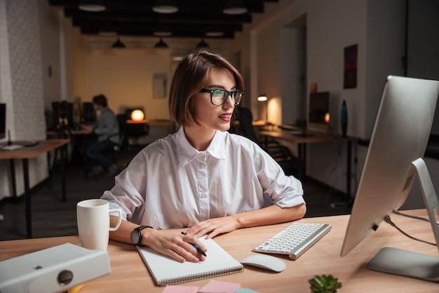 Feliz bastante joven empresaria en gafas escribiendo y usando la computadora en la oficina