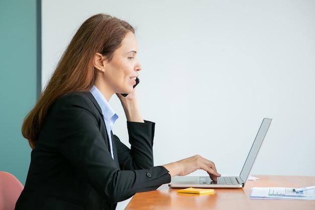 Feliz bastante joven empresaria hablando por teléfono móvil y sonriendo, trabajando en la computadora en la oficina, usando la computadora portátil en la mesa