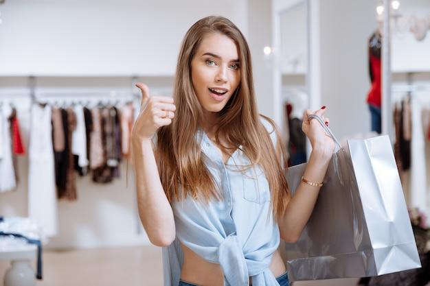 Feliz bastante joven sosteniendo el bolso de compras y mostrando los pulgares para arriba en la tienda de ropa