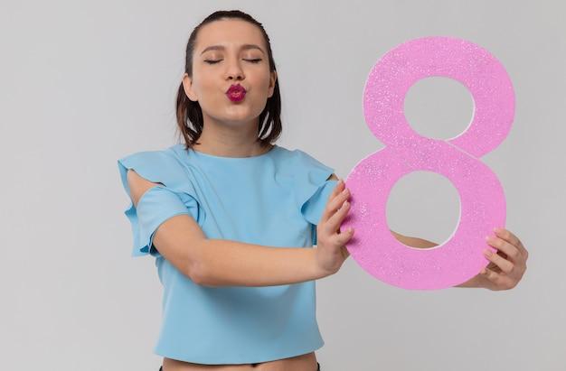 Feliz bastante joven sosteniendo rosa número ocho y enviando beso