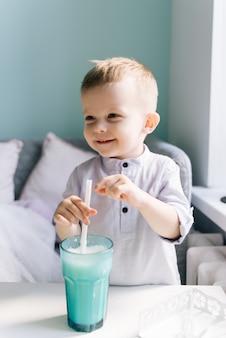 Feliz bebé con estilo en un café para niños bebiendo un batido