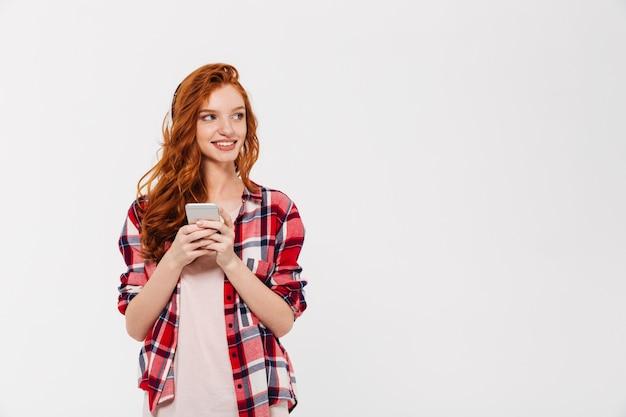 Feliz bella joven pelirroja dama chateando por teléfono móvil.