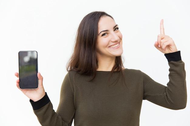 Feliz bella mujer alegre que muestra la pantalla del teléfono inteligente en blanco